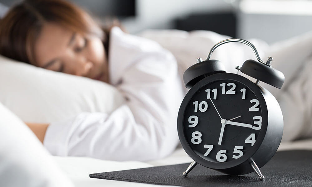 Alarm Clock Next to Sleeping Woman