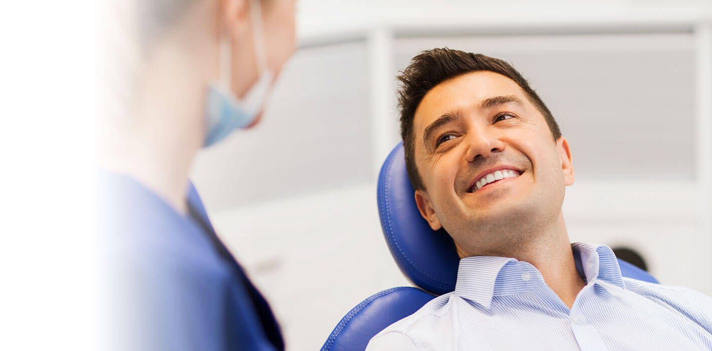 A man laying back in a dental treatment chair. looking at the dental assistant