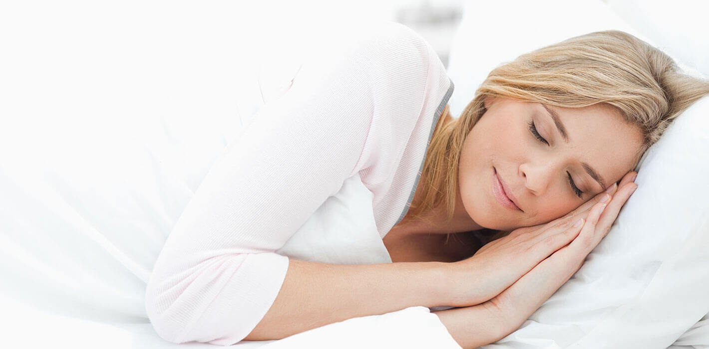 A woman with blonde hair and wearing a white shirt, sleeping peacefully on her left side